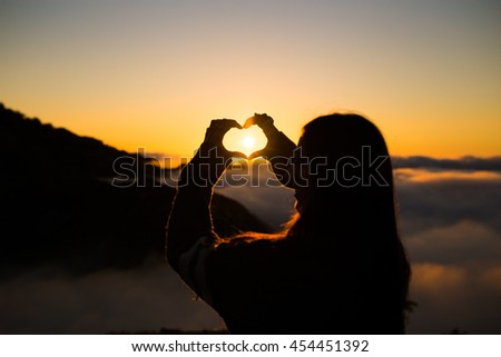 Girl doing a heart with her hands and the sun - stock photo