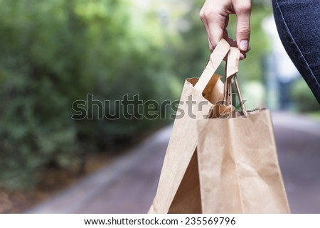 Girl doing ecological shopping with paper bags in hand - stock photo
