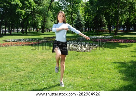 Girl doing exercise for the legs outdoors in the park against the backdrop of greenery