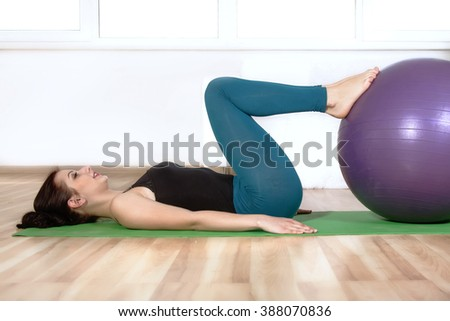 Girl doing exercises lying on the floor. She makes the press putting her foot on the gym ball. Concept: lifestyle, fitness, aerobics and health.