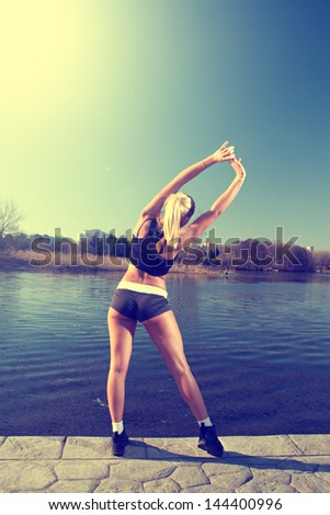 Girl doing exercises on the River - stock photo