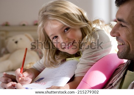 Girl (6-8) doing homework by father, smiling, portrait - stock photo