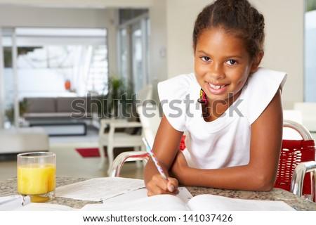 Girl Doing Homework In Kitchen - stock photo