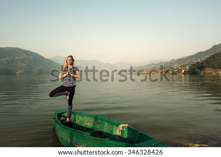 Girl doing morning sports fitness exercises near  mountain lake outdoor. Yoga tour, relaxation - stock photo