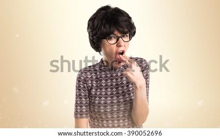 Girl doing vomiting gesture over ocher background - stock photo