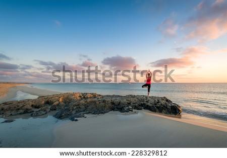 Girl doing yoga at Formentera beach. Wonderful sunrise scene. - stock photo