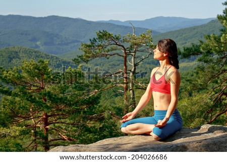 girl doing yoga on the rocks of the coniferous forest