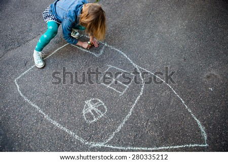 Girl drawing a picture of a house with street chalk on asphalt - stock photo