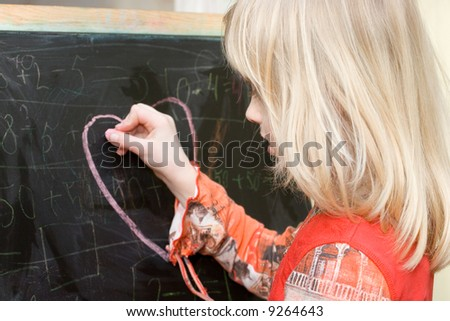 Girl drawing heart on the board