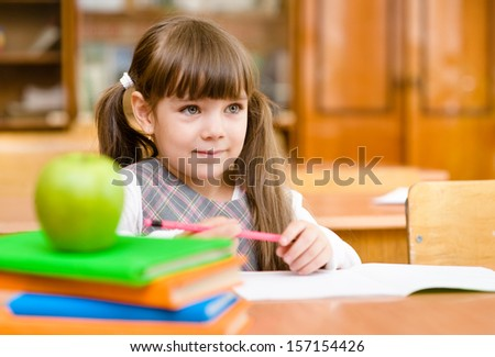 girl drawing in copybook in classroom - stock photo