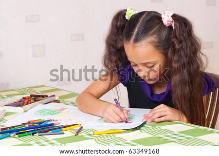 Girl drawing with crayons at the table - stock photo