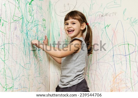 girl drawing with crayons on the wallpaper - stock photo