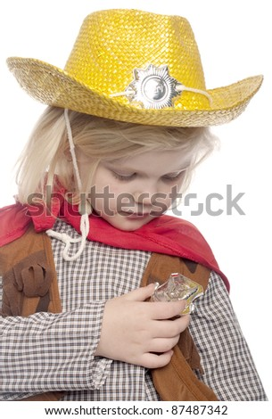Girl dressed as a cowgirl. is looking directly down at her hand holding her cowgirl badge