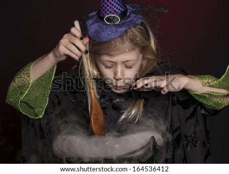 girl dressed as Halloween witch with cauldron isolated on dark red background
