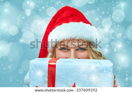 Girl dressed in santa hat  with a Christmas gift. She looking at camera. Holiday concept with blue background. - stock photo