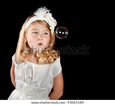Girl dressed in white on black background blowing bubble
