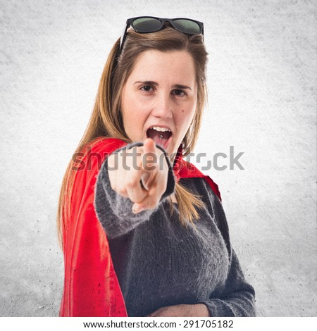 Girl dressed like superhero pointing front over textured background - stock photo