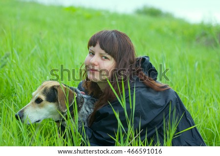 girl dressiruem dog outdoor. hound in grass fields with hostess