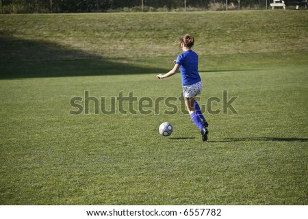 Girl dribbling a soccer ball before a match. - stock photo