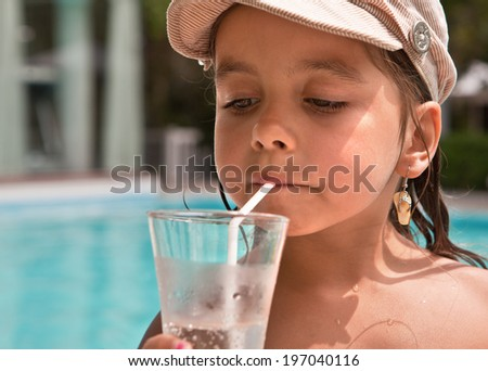 Girl drinking a cold drink from the tubes on the background of the pool - stock photo