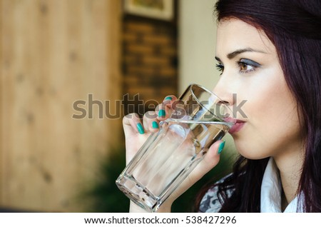 Girl drinking a glass of water in a coffee shop or office. Hand of business girl holding a glass of water and drink close-up