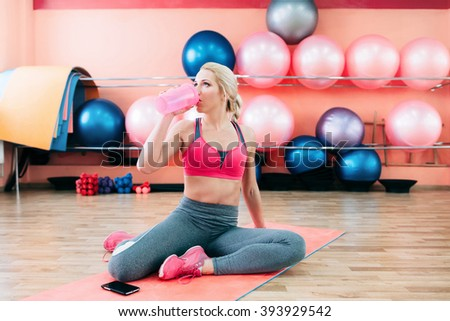 Girl drinking protein shake after training. Sporty woman sitting on yoga mat after some exercises drinks protein shake. Sporty girl sitting on yoga mat after some exercises drinks sports nutrition. - stock photo