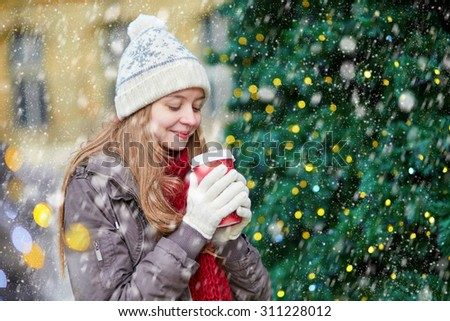 Girl drinking take away coffee, hot chocolate or eggnog near decorated Christmas tree during snowfall - stock photo