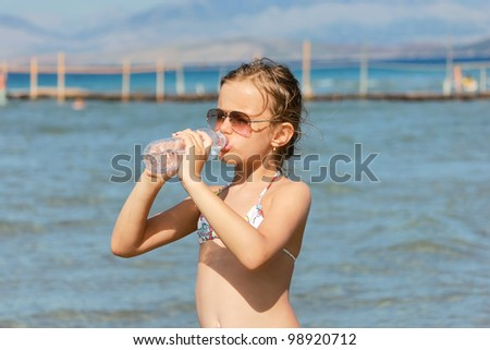 Girl drinking water on the beach