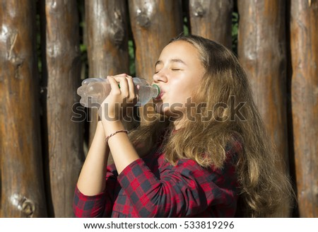 Girl drinks water from a plastic bottle