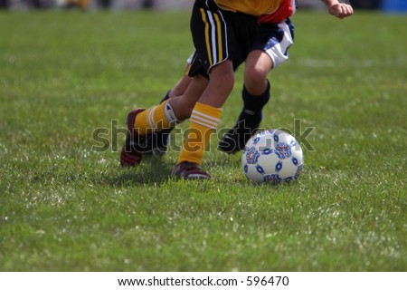 Girl drives past her competitor during a kids soccer game. - stock photo