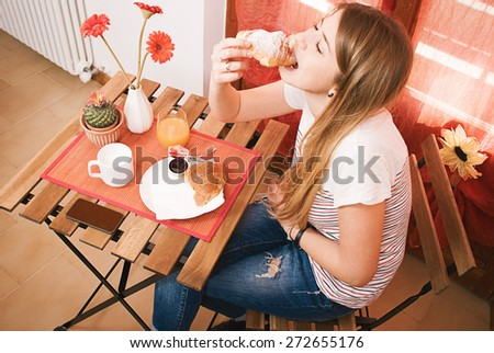 Girl during continental breakfast, selective focus on the table - stock photo
