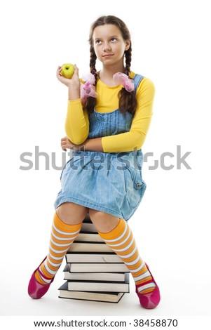 Girl eat apple sitting on pile of books,isolated on white - stock photo