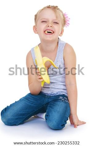 Girl eating a banana.Very cheerful little girl. - stock photo
