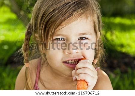 Girl eating a carrot - stock photo