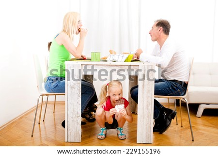 Girl eating chocolate beneath table while the family is having breakfast  - stock photo