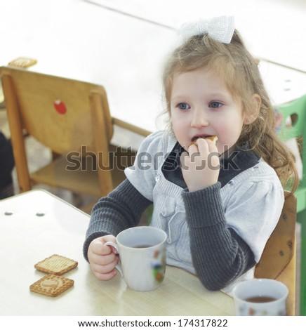 Girl eating chocolate cakes - stock photo