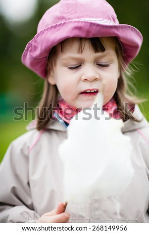 """Girl eating cotton candy - """"What sticky cotton candy"""" - portrait of a distressed girl with cotton candy. Shallow depth of field - stock photo"""