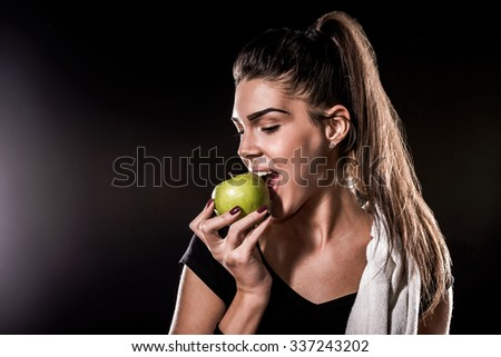 Girl Eating Green Apple on Black Background - stock photo