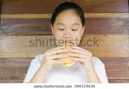 Girl eating hamburger - stock photo
