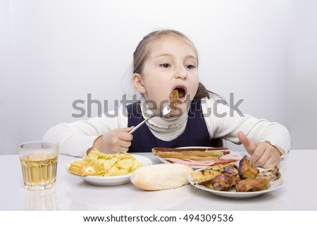 girl eating harmful fatty foods. Potatoes, chips, chicken, meats, bread, soda. eating harmful fatty foods. Potatoes, chips, chicken, meats, bread, soda. nutrition student,  good proper nutrition
