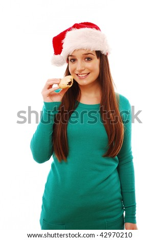 Girl eating mince pie on white isolated background - stock photo