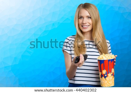 girl eating popcorn and watching tv - stock photo