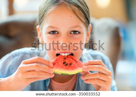 Girl eating watermelon - Portrait of a beautiful young girl eating watermelon - Caucasian model - stock photo