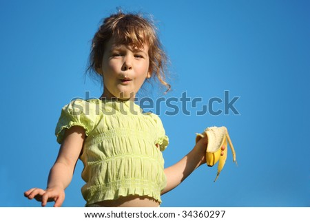 girl eats banana against blue sky - stock photo