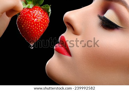 Girl eats strawberries on a black background - stock photo