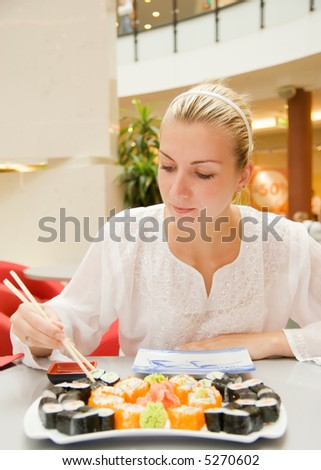 Girl eats sushi in a restaurant - stock photo