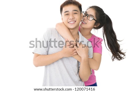 Girl embracing her boyfriend and looking at camera - stock photo