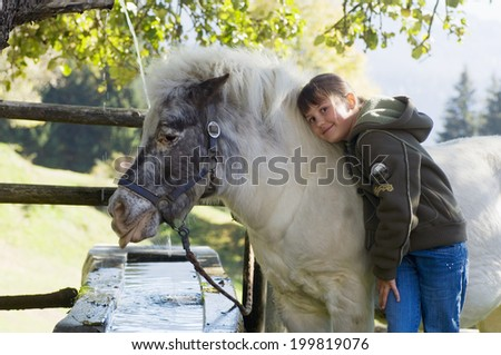 Girl embracing pony at fountain - stock photo