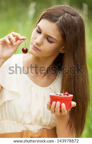 Girl enjoying cherries in the park