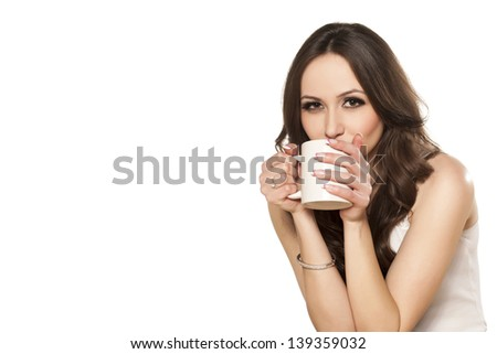 girl enjoys her cup of tea on white background - stock photo